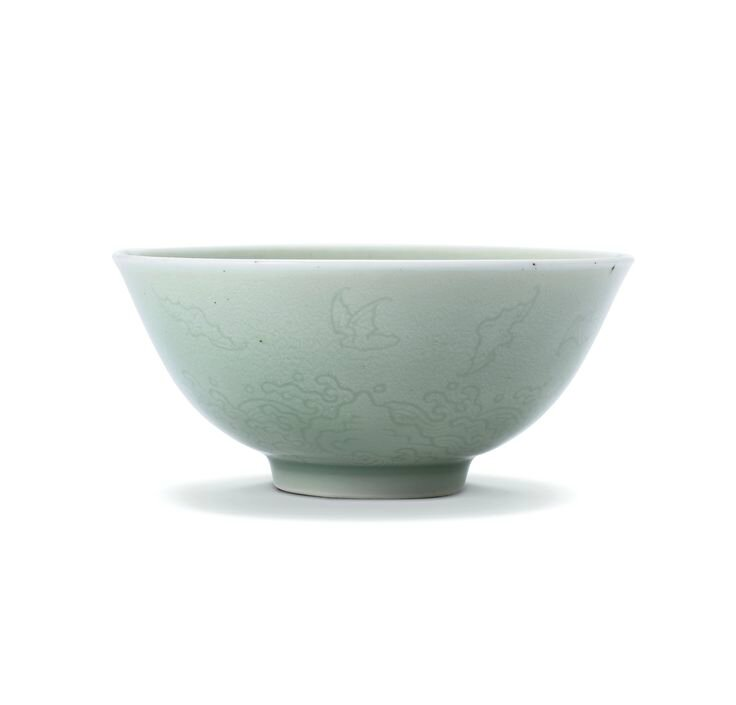 A celadon-glazed incised 'bats and waves' bowl, Mark and period of Yongzheng
