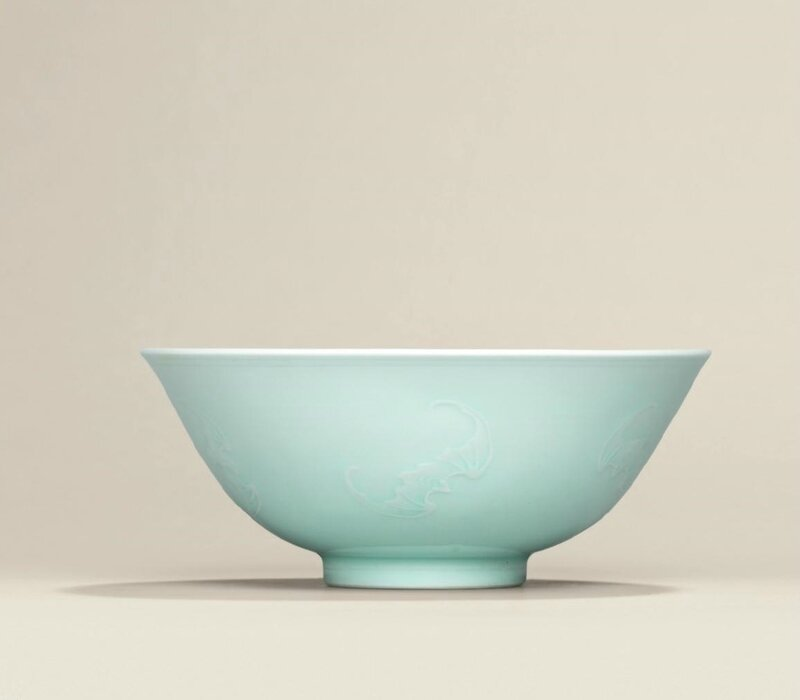 A carved pale celadon-glazed 'bats' bowl, Yongzheng six-character mark in underglaze blue within a double circle and of the period (1723-1735)