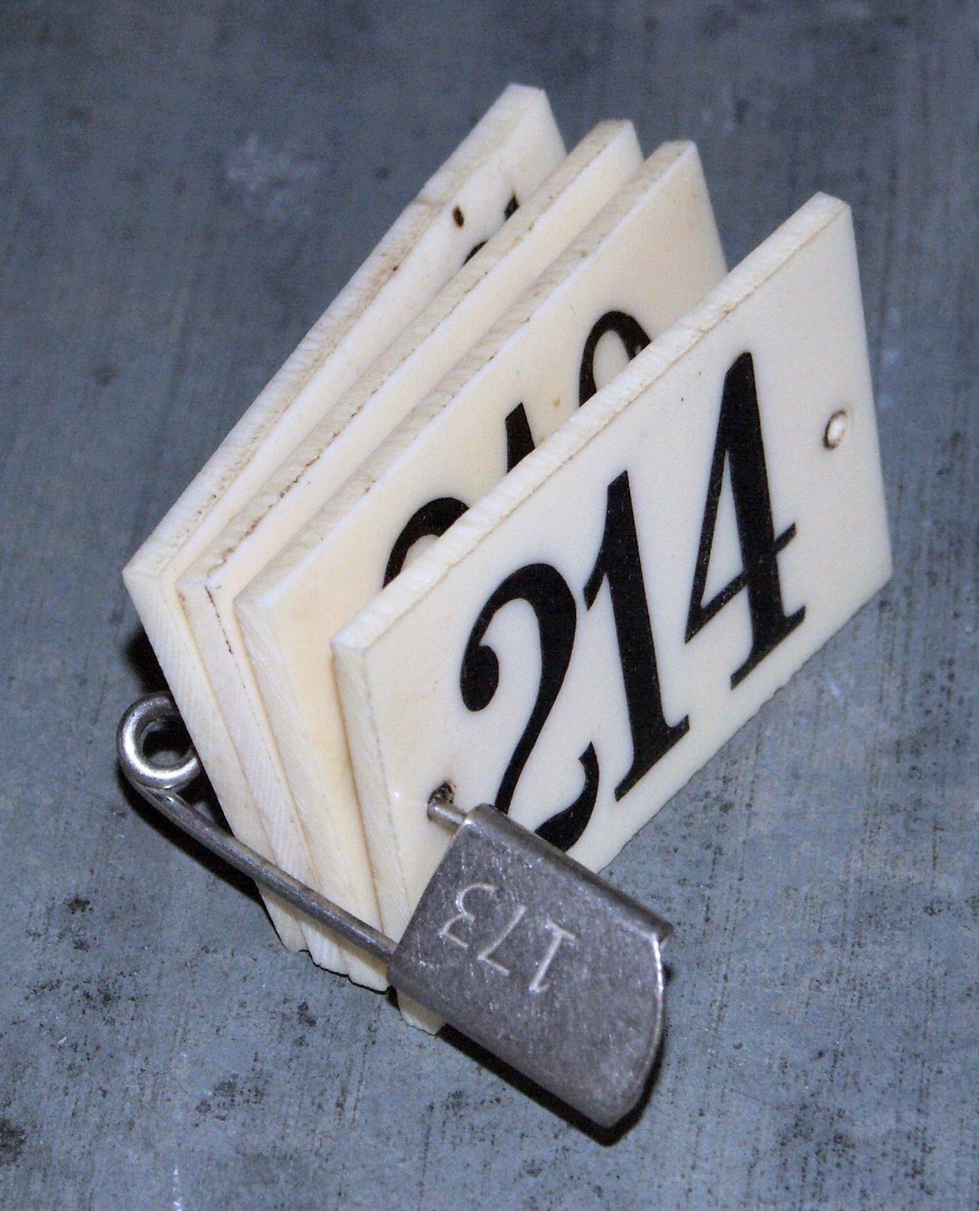 En celluloïd gravé. numéro peint en noir. deux trous de fixation