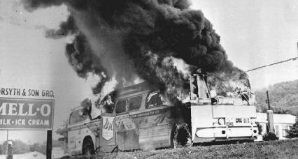 A Freedom Rider bus goes up in flames after a fire bomb was tossed through a window in 1961 in Alabama. AP Images.