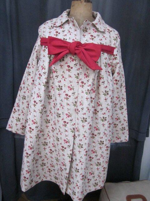 Un manteau AGLAE en lin brut à fleurettes et neoud rouge...
