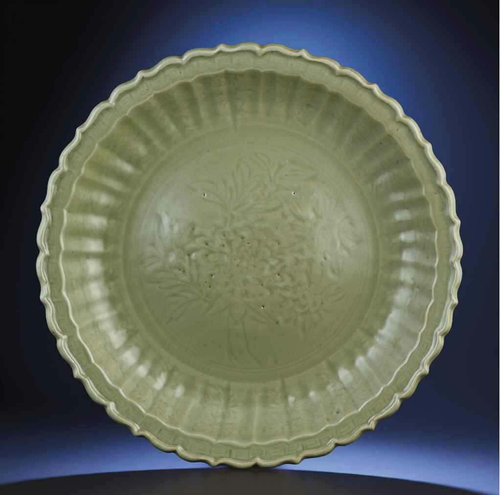 A fine large carved 'peony' Longquan celadon barbed-rim charger, Hongwu period (1368-1398)