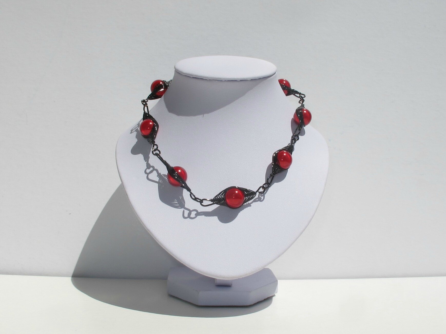collier wire noir perles rouges buste blanc