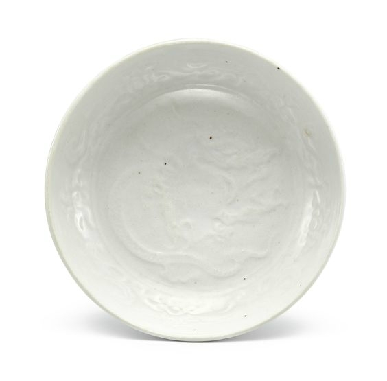 A white-glazed moulded 'dragon' dish, Yuan dynasty (1279-1366)