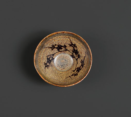 A small tortoise-glazed Jizhou bowl with prunus decoration at the inside