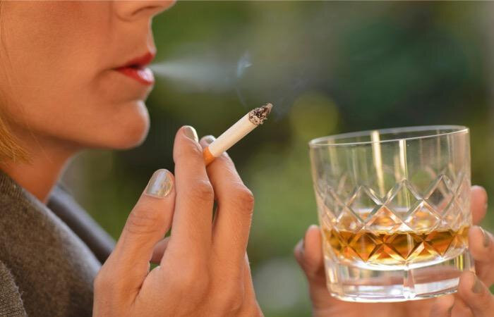 woman-drinking-a-glass-of-whiskey-and-smoking-a-cigarette-picture-id902089248-1545995481