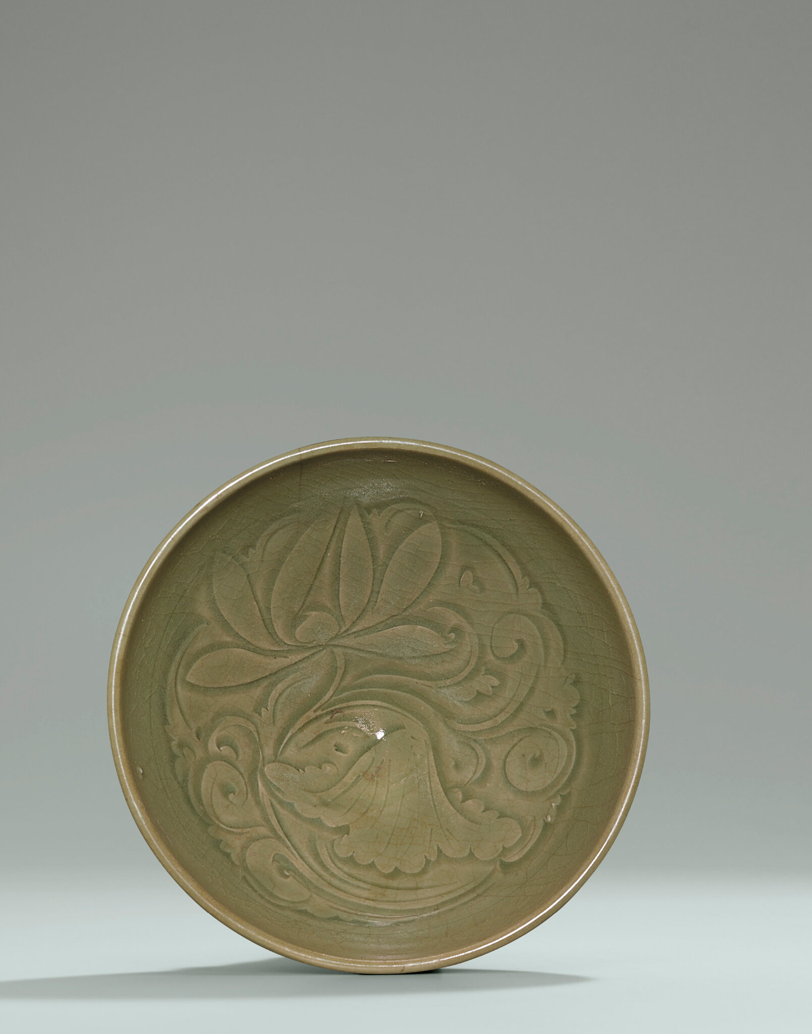 A Yaozhou carved celadon 'Peony' conical bowl, Northern Song Dynasty, (960-1127)