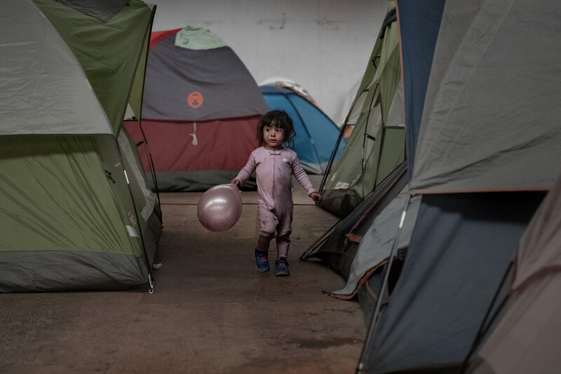 A migrant child shelters in a warehouse as her parents wait to claim asylum in the US