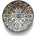 A kashan blue and black pottery bowl with palmettes, persia, early 13th century