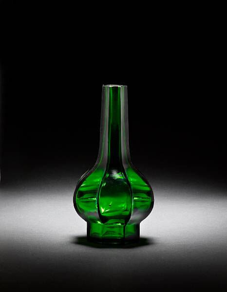 An octagonal facetted green glass bottle vase, Qianlong wheel-cut four-character mark and of the period (1736-1795)