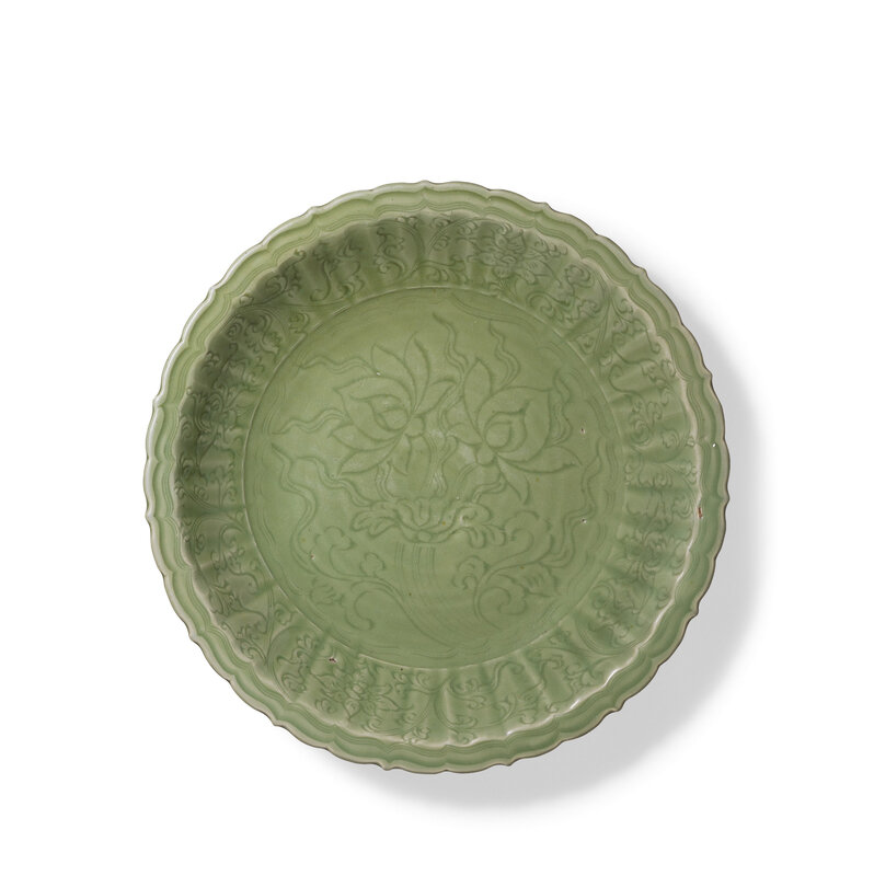 A large carved Longquan celadon 'lotus' barbed-rim dish, Early Ming Dynasty