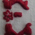 E petite fleur, brodé en rouge sombre sur un petit coeur